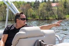 Uomini che indicano dito su una barca Fotografia Stock