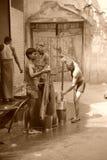 Uomini che lavano seppia dei vestiti. Vecchia Delhi, India. fotografie stock libere da diritti