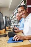 Uomini che lavorano ai computer in biblioteca Fotografie Stock Libere da Diritti