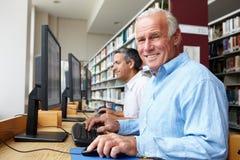 Uomini che lavorano ai computer in biblioteca Immagine Stock