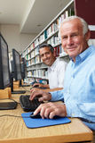 Uomini che lavorano ai computer in biblioteca Immagini Stock Libere da Diritti