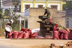 Uomini che lavorano al vaglio dei chicchi di caffè sulla via l'11 febbraio 2012 in Nam Ban, Vietnam Immagini Stock Libere da Diritti