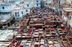 Uomini che lavorano duro nel souk della conceria a Fes, Marocco Immagine Stock