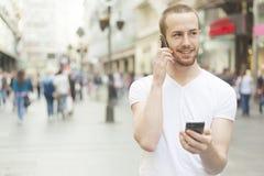 Uomini che parlano sul telefono mobile e che giudicano secund Fotografia Stock Libera da Diritti