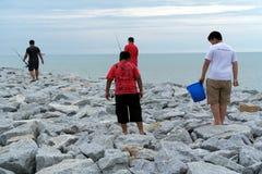 Uomini che pescano alla spiaggia Immagini Stock