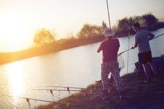 Uomini che pescano nel tramonto e che si rilassano mentre godendo dell'hobby fotografie stock