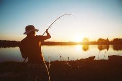 Uomini che pescano nel tramonto e che si rilassano mentre godendo dell'hobby fotografia stock