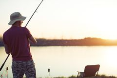 Uomini che pescano nel tramonto e che si rilassano mentre godendo dell'hobby immagini stock libere da diritti