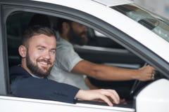 Uomini che posano nella cabina dell'automobile nel concessionario auto immagine stock libera da diritti