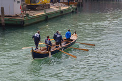Uomini che remano una barca a Venezia Immagine Stock