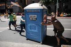 Uomini che rotolano via una toilette Fotografia Stock