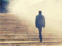 Uomini che scalano le scale nella nebbia al futuro incerto immagini stock libere da diritti
