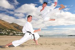 Uomini che si esercitano in karatè sulla spiaggia Fotografia Stock Libera da Diritti