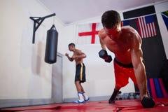Uomini che si esercitano nello studio di forma fisica Fotografia Stock Libera da Diritti