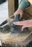 Uomini che spianano una plancia di legno con un aereo elettrico Fotografia Stock
