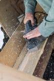 Uomini che spianano una plancia di legno con un aereo elettrico Immagini Stock Libere da Diritti