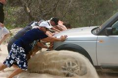 Uomini che spingono automobile bogged Fotografia Stock Libera da Diritti
