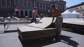 Uomini che sviluppano fase per l'evento di estate sulla via I lavoratori portano i bordi di legno stock footage