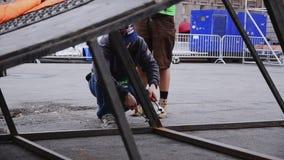 Uomini che sviluppano fase per l'evento sulla via Fissi gli ostacoli del ferro Operaio costruzione video d archivio