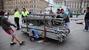 Uomini che sviluppano fase per l'evento sulla via I lavoratori portano gli ostacoli del ferro sul carretto La gente stock footage