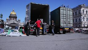 Uomini che sviluppano fase per l'evento sulla via I lavoratori portano l'attrezzatura dal camion stock footage