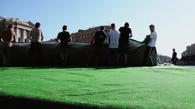 Uomini che sviluppano fase per l'evento sulla via I lavoratori portano la tenda enorme Tappeto verde video d archivio