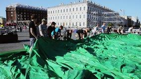 Uomini che sviluppano fase per l'evento sulla via I lavoratori portano la tenda verde enorme sunny video d archivio