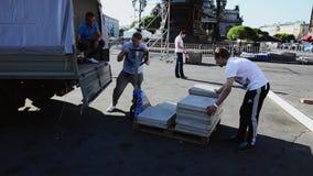 Uomini che sviluppano fase per l'evento sulla via I lavoratori portano le mattonelle sul carretto per trasportare stock footage