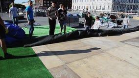 Uomini che sviluppano fase per l'evento sulla via I lavoratori presentano il tappeto verde enorme stock footage