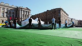Uomini che sviluppano fase per l'evento sulla via I lavoratori tengono la tenda verde enorme sunny stock footage