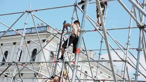 Uomini che sviluppano fase per l'evento sulla via Scala di aumento dei lavoratori Ostacoli del ferro sunny stock footage