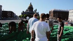 Uomini che sviluppano fase sulla via I lavoratori portano la tenda verde enorme St Petersburg video d archivio