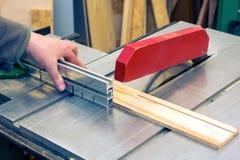 Uomini che tagliano legno con la sega circolare immagine stock