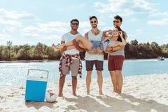 Uomini che tengono donna sorridente in mani e che esaminano macchina fotografica sulla spiaggia Immagini Stock