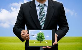 Uomini che tengono l'ambiente ed ecologia di tecnologia della compressa del touch screen immagini stock libere da diritti