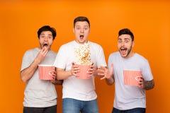 Uomini colpiti che mangiano popcorn e che guardano film spaventoso fotografia stock