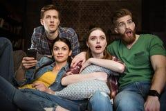 Uomini colpiti e donne che guardano film Immagine Stock