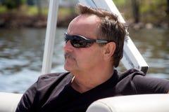 Uomini con gli occhiali da sole su una barca Fotografie Stock Libere da Diritti