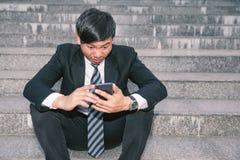 Uomini d'affari asiatici con le emicranie o le emicranie al comune dopo le immagini di giovani uomini d'affari che sono stanchi,  fotografie stock libere da diritti
