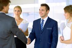 Uomini d'affari che agitano le mani Due uomini d'affari sicuri che stringono le mani e che sorridono mentre stando all'ufficio in Fotografia Stock