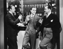 Uomini d'affari che bevono insieme alla barra (tutte le persone rappresentate non sono vivente più lungo e nessuna proprietà esis Immagine Stock