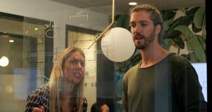 Uomini d'affari che discutono sopra la parete di vetro nell'ufficio 4k archivi video