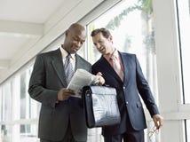 Uomini d'affari che leggono giornale in ufficio Immagini Stock Libere da Diritti