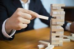 Uomini d'affari che selezionano i blocchi di legno per riempire i domino mancanti Concetto crescente di affari immagine stock libera da diritti