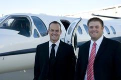 Uomini d'affari che si levano in piedi davanti al jet corporativo Immagine Stock Libera da Diritti