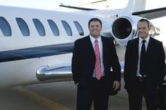 Uomini d'affari che si levano in piedi davanti al jet corporativo Fotografia Stock