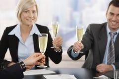 Uomini d'affari che sollevano pane tostato con champagne Fotografia Stock