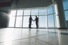 Uomini d'affari che stringono le mani dentro contro le finestre panoramiche Fotografie Stock