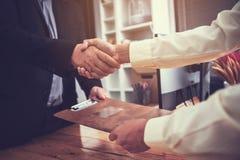 Uomini d'affari che stringono le mani dopo con successo il completamento del inve immagini stock libere da diritti