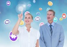 Uomini d'affari che toccano le icone dell'applicazione digitalmente generate fotografia stock